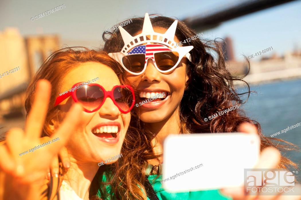 Stock Photo: Women taking picture of themselves in novelty sunglasses.