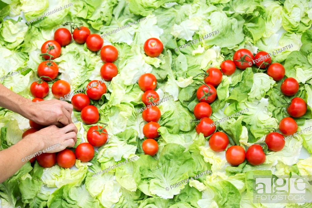 Stock Photo: Germany, Human hand forming bio letters with tomatoes on cabbage leaf.