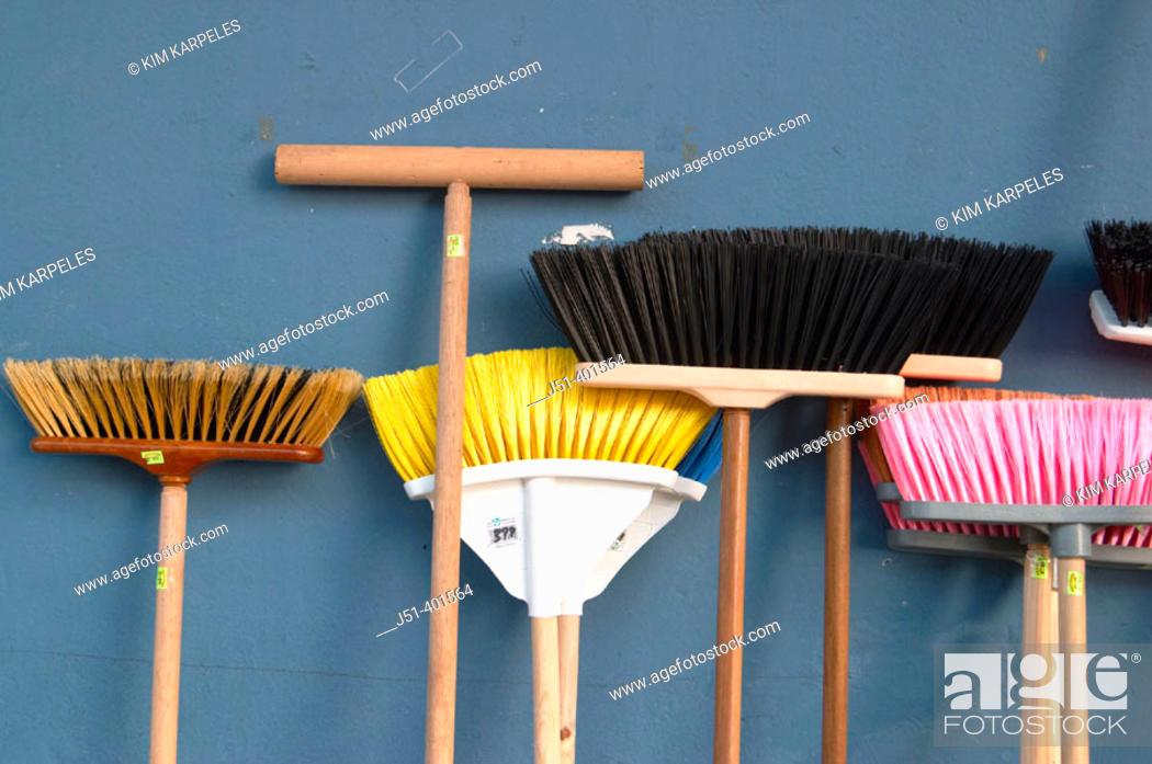 Stock Photo: PUERTO RICO  San Juan. Variety of broom shapes and colors, lean against blue wall, Plaza del Mercado.