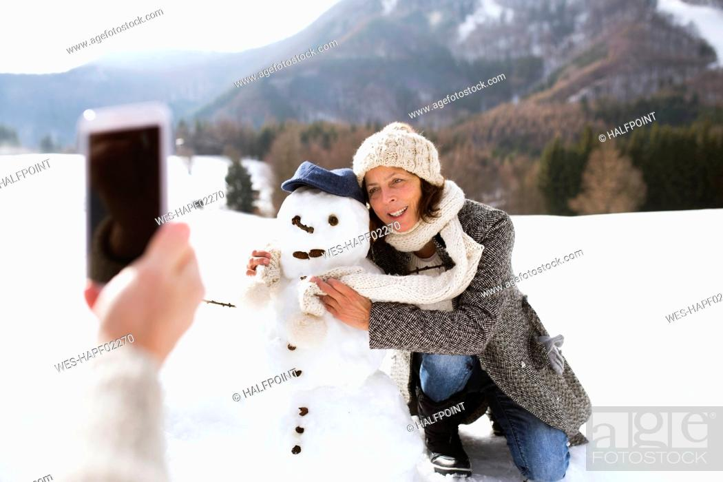 Stock Photo: Senior man taking picture of his wife with snowman.