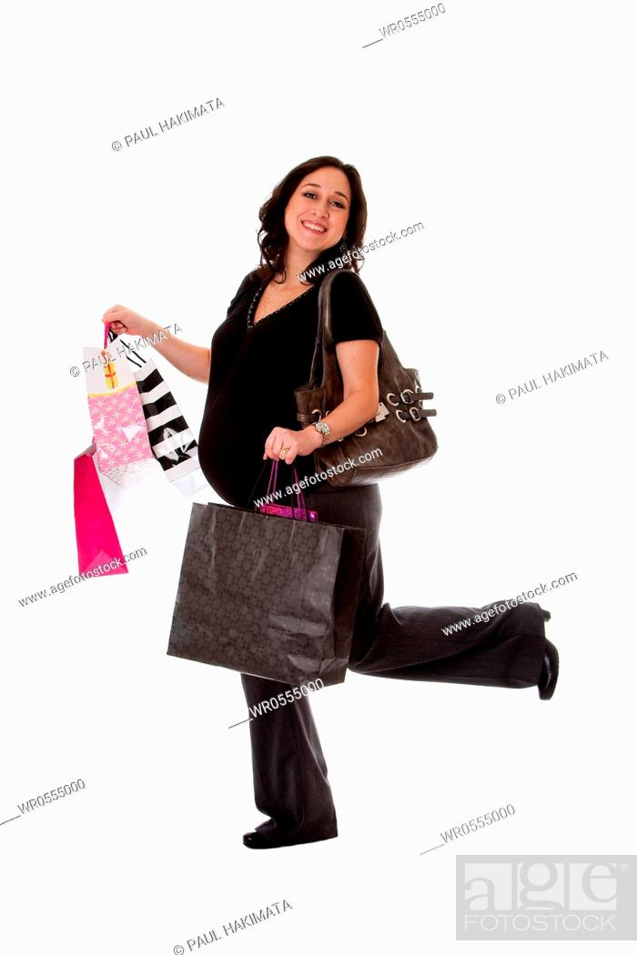 Stock Photo: Beautiful happy exciting smiling Caucasian pregnant brunette woman holding shopping bags while walking and having her leg up, isolated.