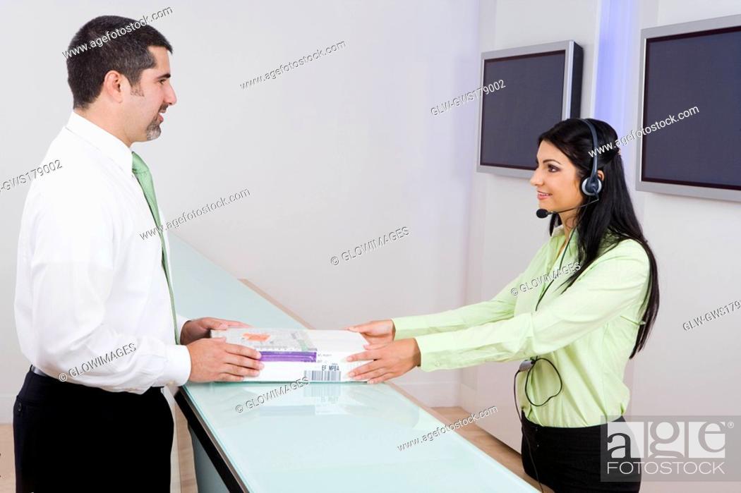 Stock Photo: Side profile of a female customer service representative giving books to a businessman.