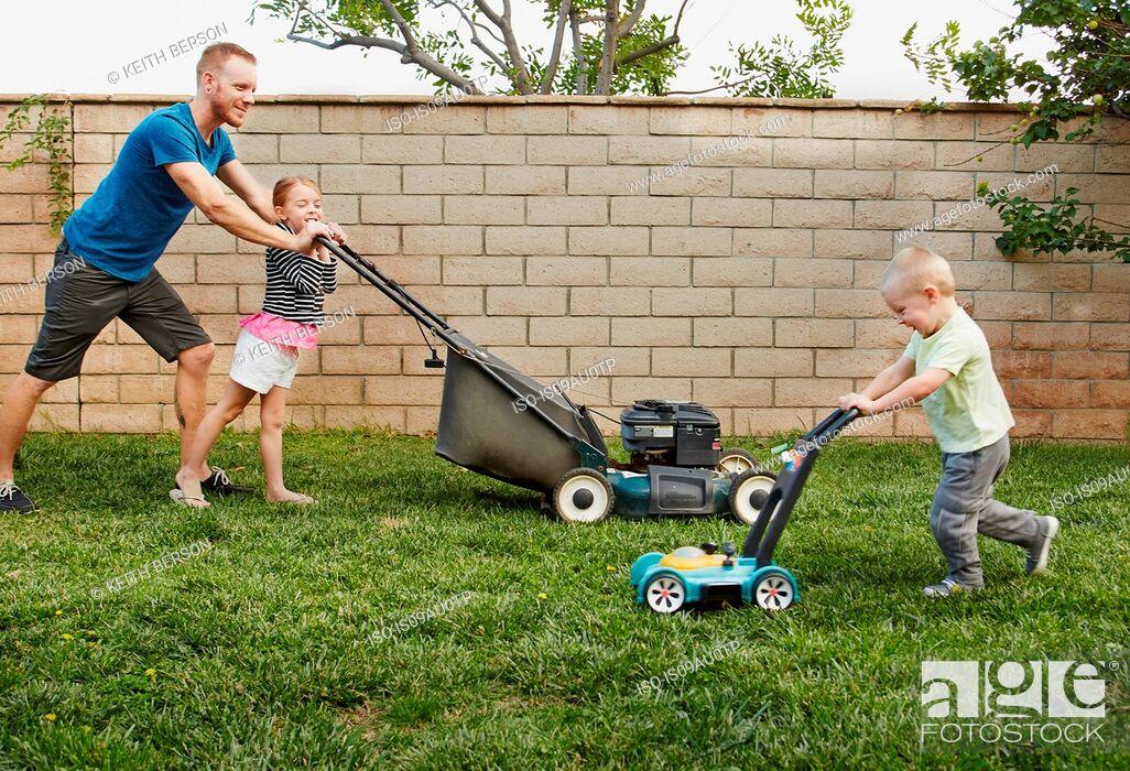 Stock Photo: Family mowing lawn in backyard.