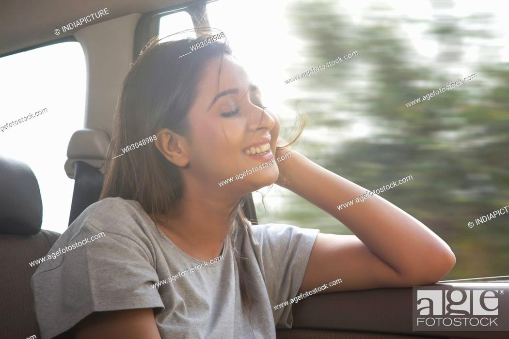 Stock Photo: Beautiful women in car hair gets blown by the wind.