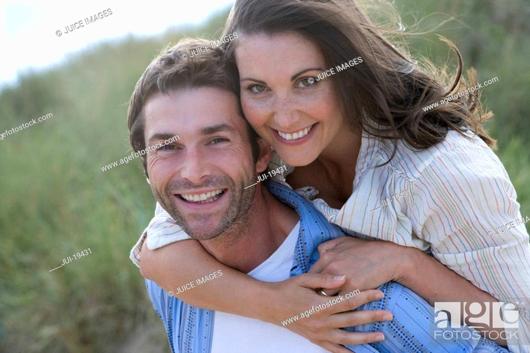 Stock Photo: Portrait of man piggybacking woman.