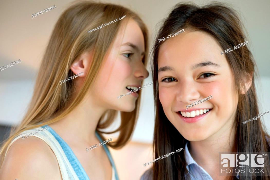 Stock Photo: Girl whispering to her friend.
