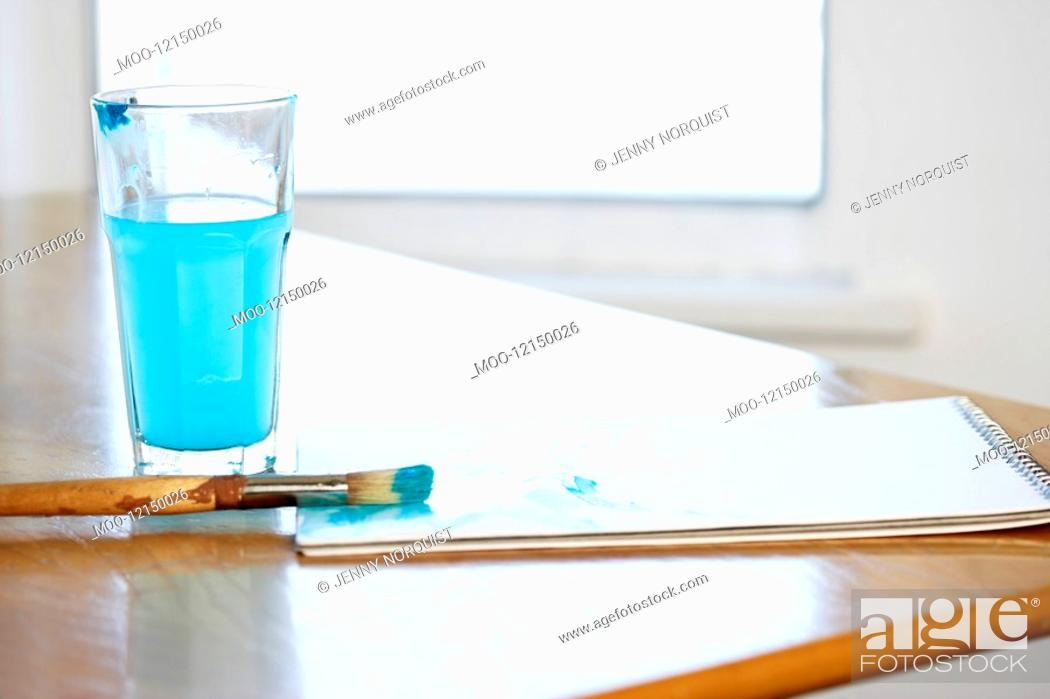 Stock Photo: Paintbrush and pad by glass of blue water.