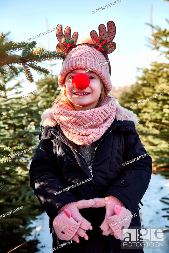 Stock Photo: Girl in christmas tree forest with red nose, portrait.