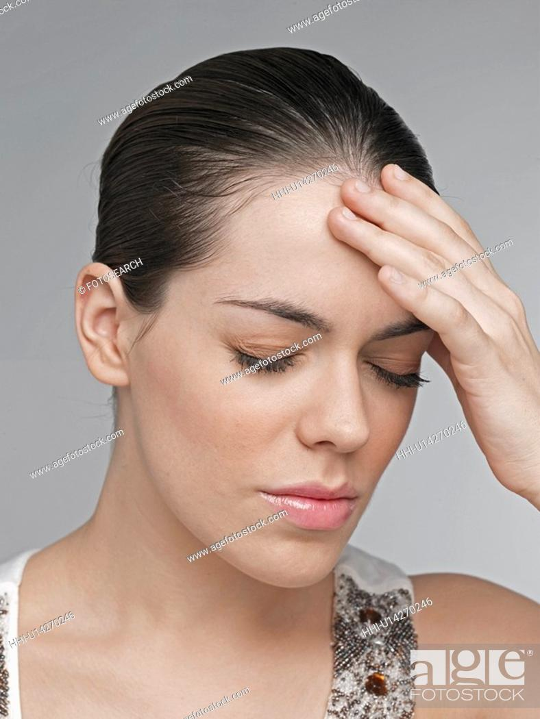 Stock Photo: Young woman with hand on forehead.