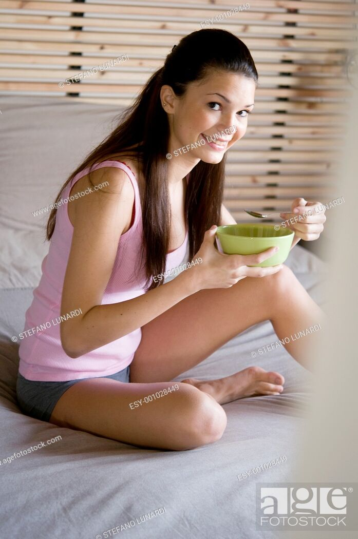 Stock Photo: Teenage girl sitting on her bed and eating.