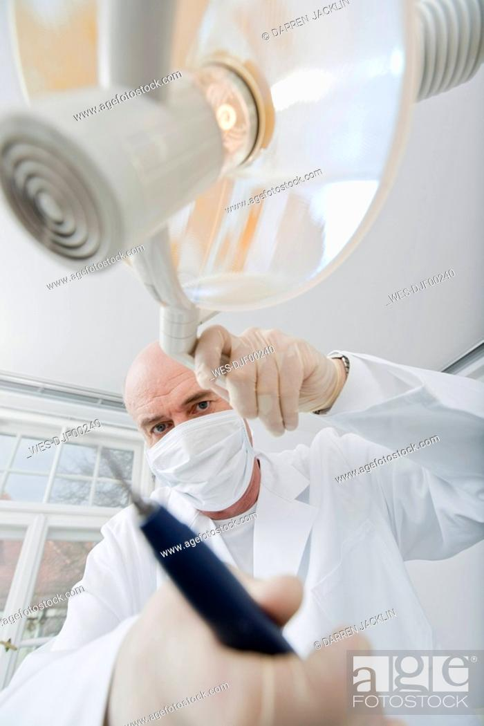 Stock Photo: Germany, Bavaria, Landsberg, Dentist wearing mask holding medical equipment,.
