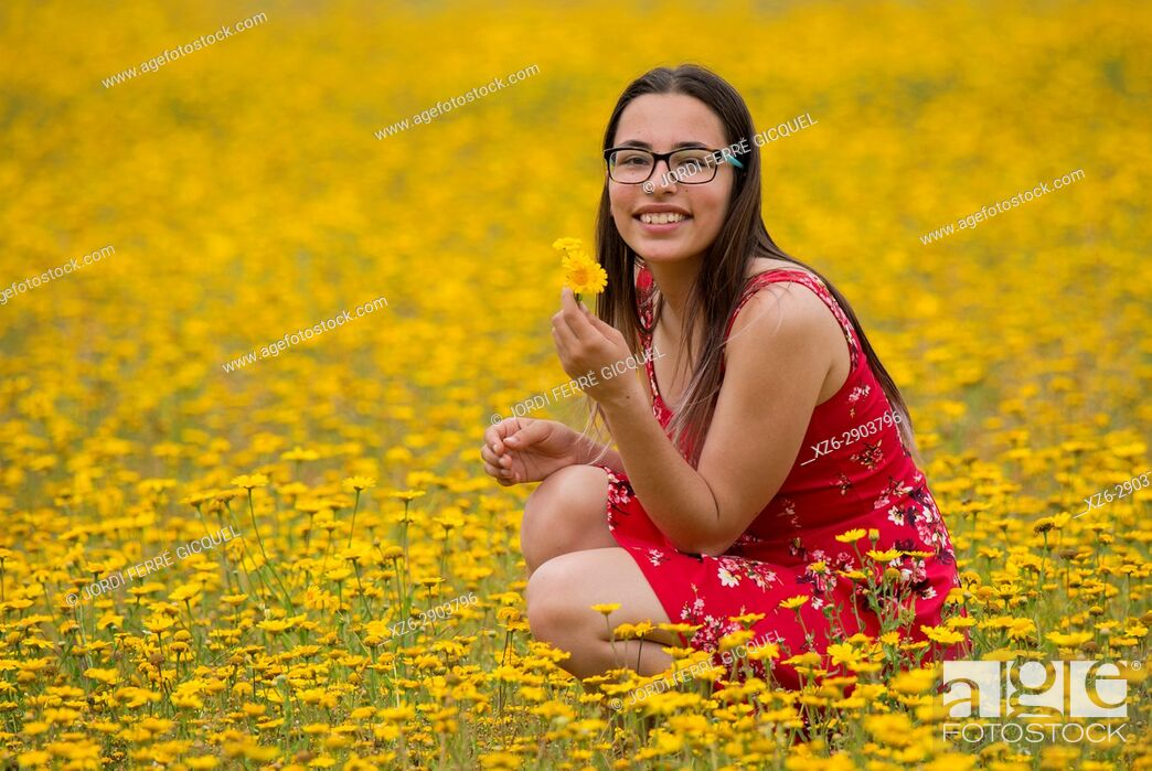 Imagen: Girl with a red dress picking up flowers in a yellow field.