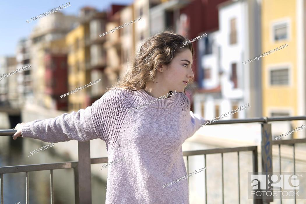 Photo de stock: Teen girl resting on a railing in the Spanish city of Orihuela. Horizontal shot with natural light.