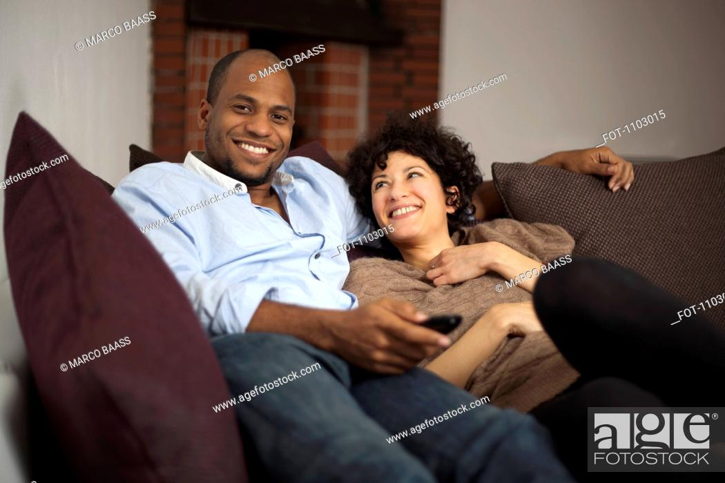 Stock Photo: A happy laughing couple relaxing on a sofa together.