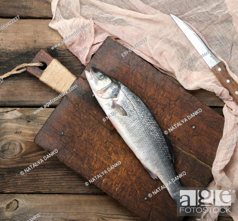 Stock Photo: fresh whole sea bass fish on brown cutting board , top view.