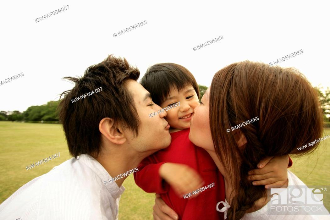 Stock Photo: A couple kiss their son amidst a vast ground.