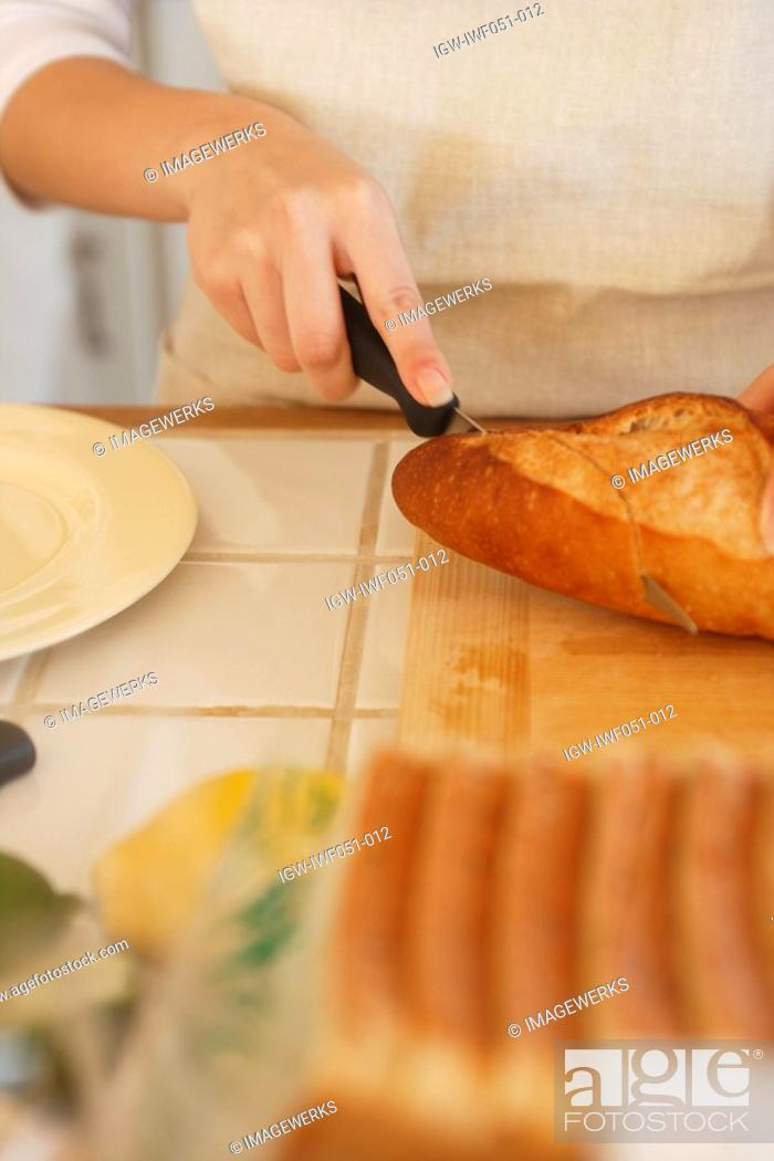 Stock Photo: Person cutting bread with knife.