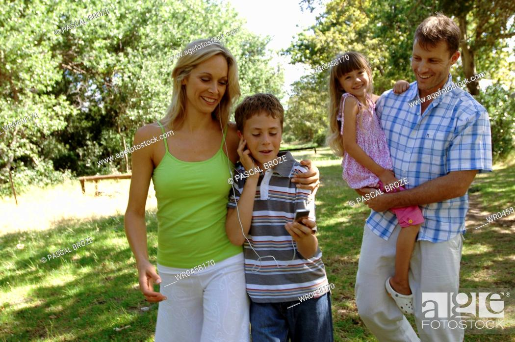 Imagen: Mid adult couple walking with their children in a park.