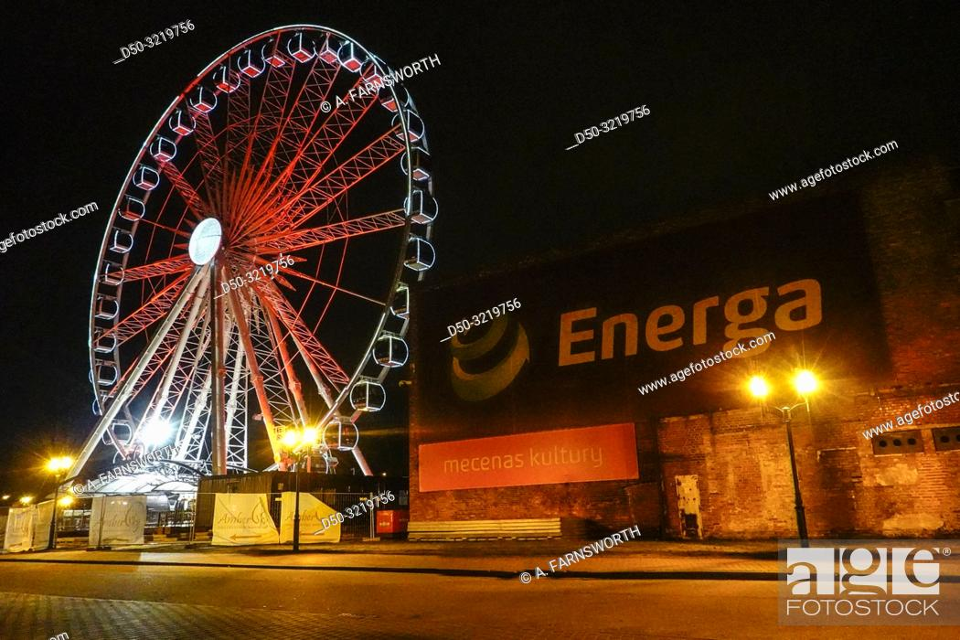 Imagen: Gdansk, Poland A Ferris wheel on a dark street in the harbor at night.