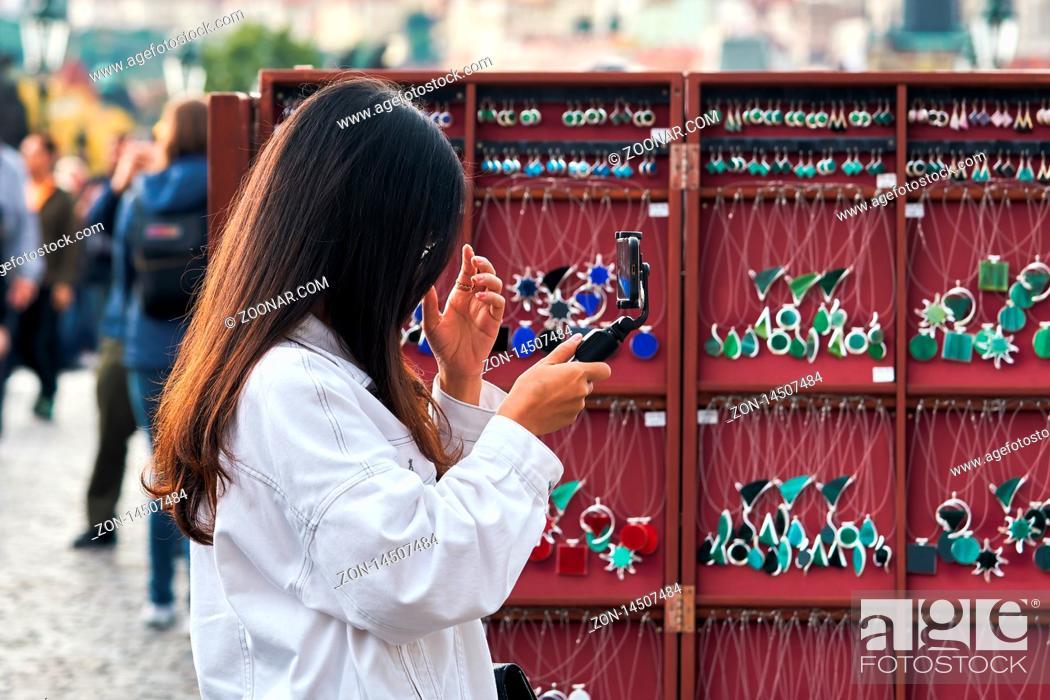 Stock Photo: Touristin aus Asien an einem Souvenir-Stand auf der Karlsbrücke in Prag.