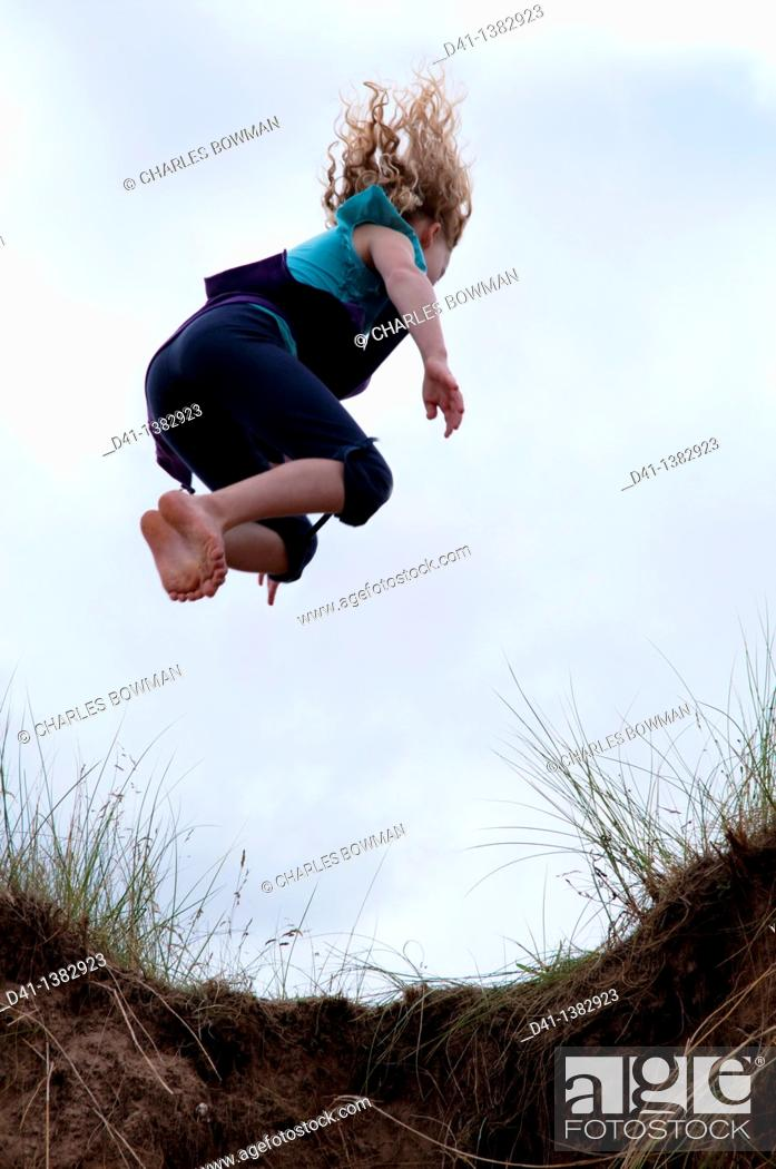 Stock Photo: child girl jumping from sand dune.