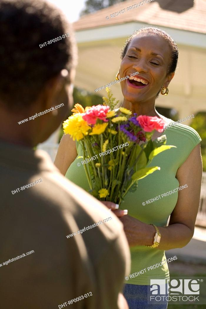 Stock Photo: A man giving a woman flowers.
