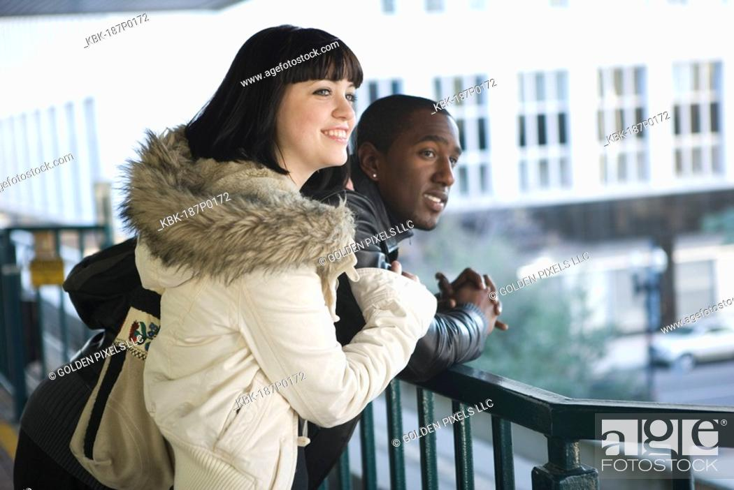 Stock Photo: Interracial couple leaning against railing overlooking city street.