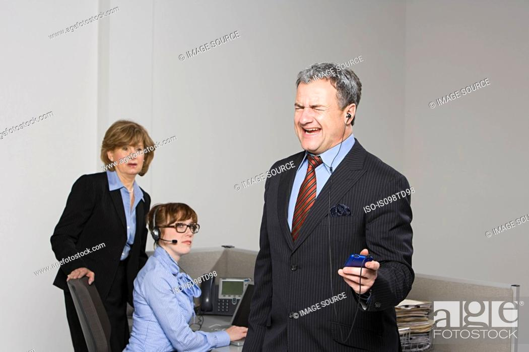 Stock Photo: Businessman listening to MP3 player.