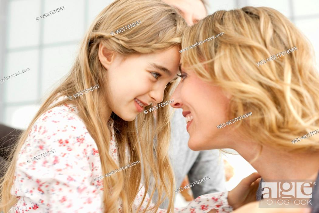 Stock Photo: Germany, Leipzig, Mother and daughter looking at each other, smiling.