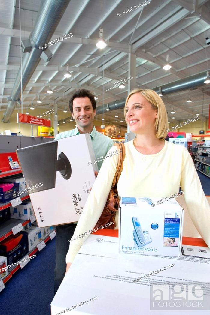Stock Photo: Young couple in shop with computers in boxes, smiling.