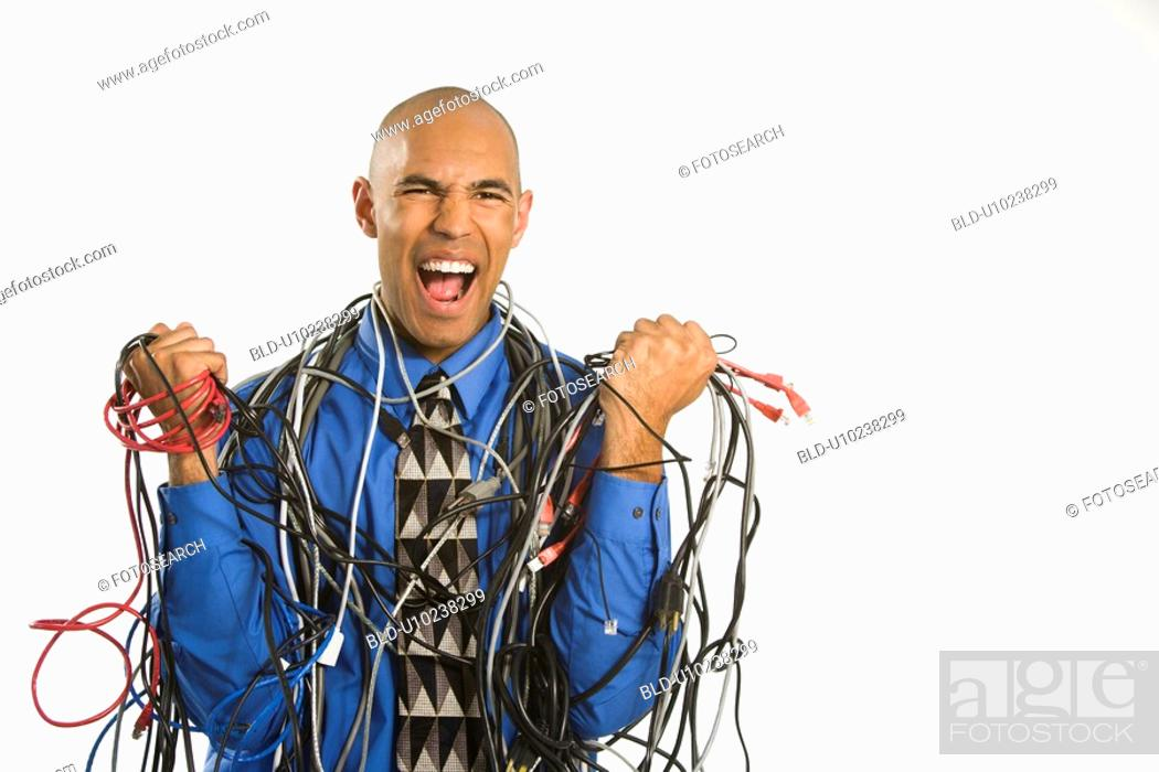 Stock Photo: Frustrated businessman wrapped in cords.