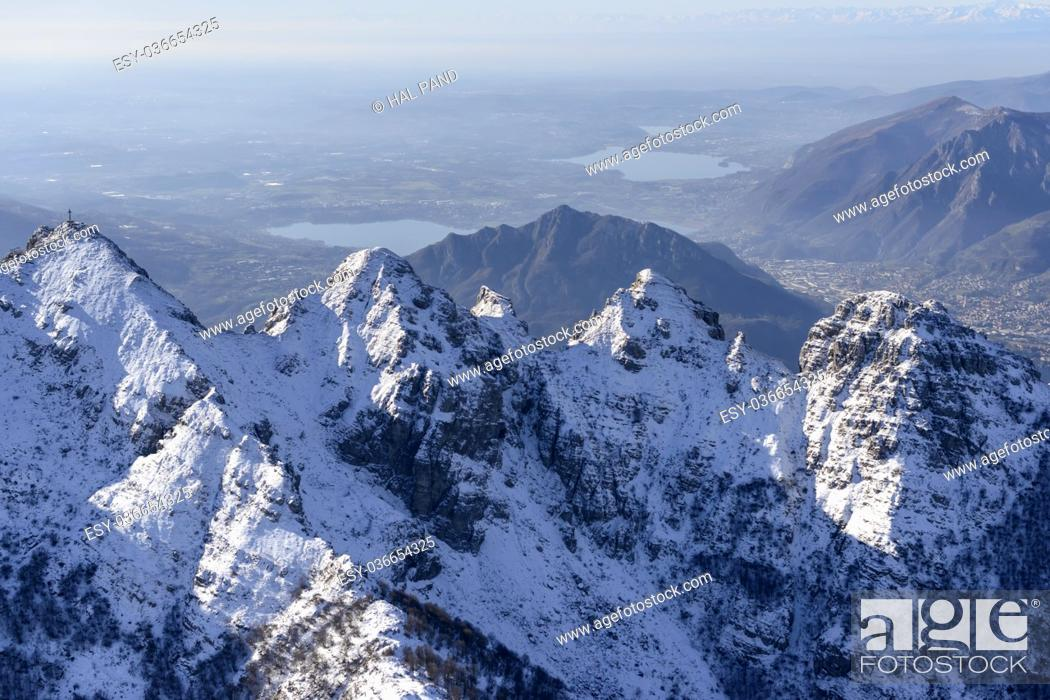 Stock Photo: aerial shot, from a small plane, of Resegone peak summit covered with the first winter snow with small lakes of Pusiano and Annone in background.