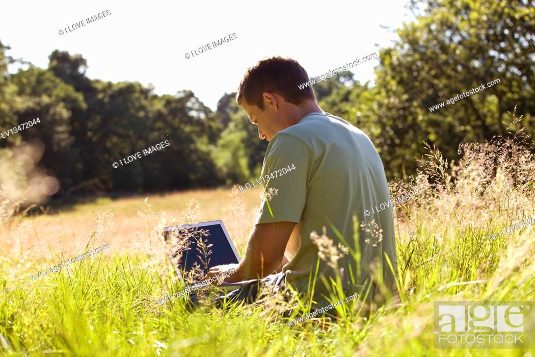 Stock Photo: A young man sitting on the grass, using a laptop.