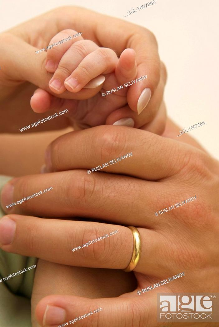 Stock Photo: Hands of happy family - parents and baby.