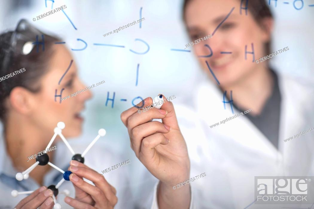 Stock Photo: Two scientists working in lab writing notes on glass pane.