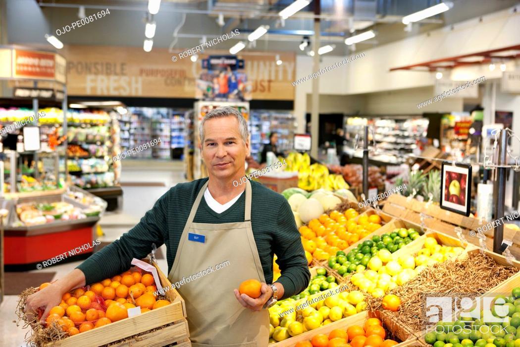 Stock Photo: Worker placing oranges in supermarket display.