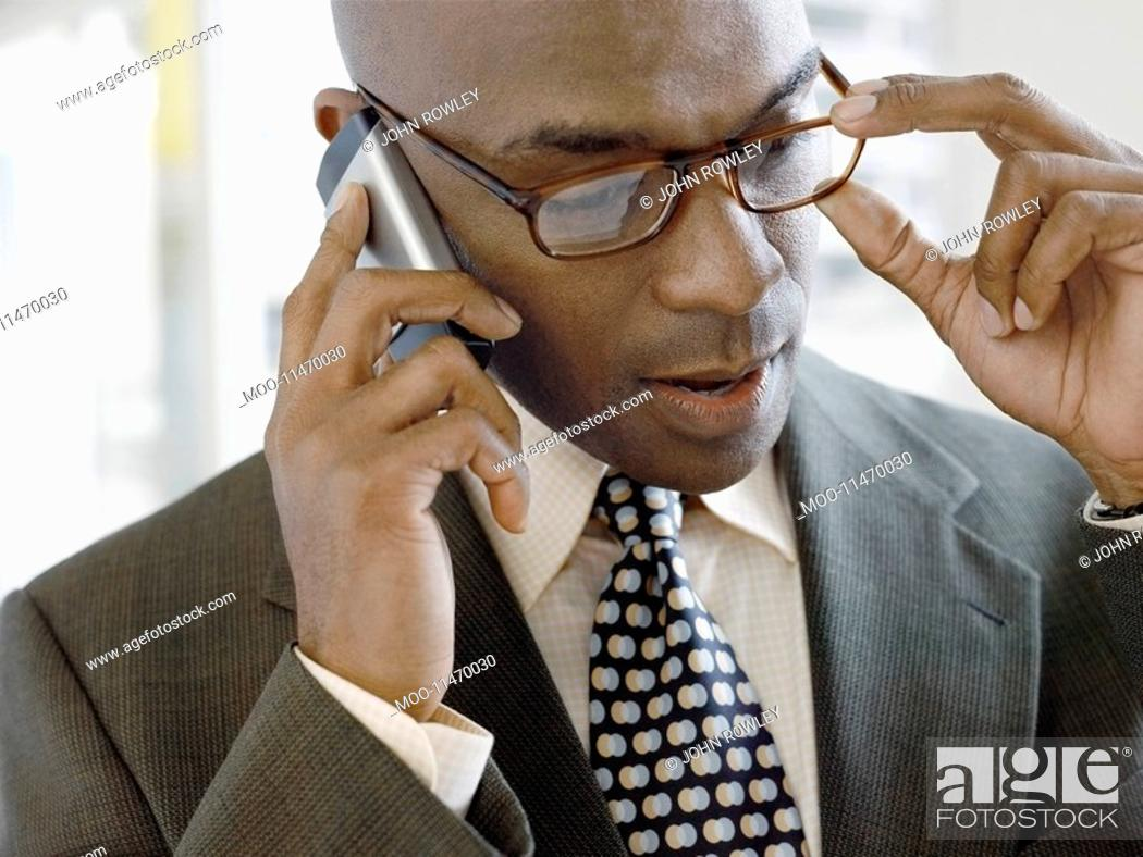 Stock Photo: Businessman using mobile phone indoors close-up.