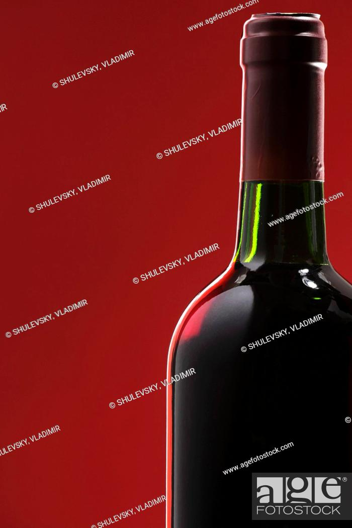 Photo de stock: Bottle of red wine against a red background.