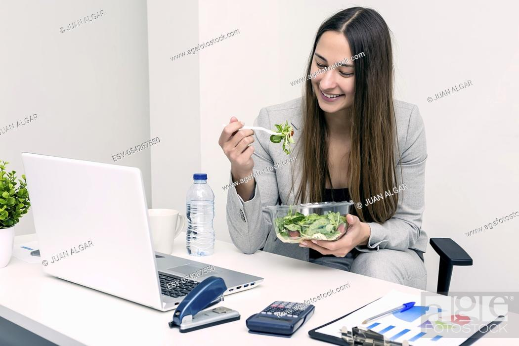 Stock Photo: Smiling young woman sitting and eating a salad in coworking space. Horizontal indoors shot.