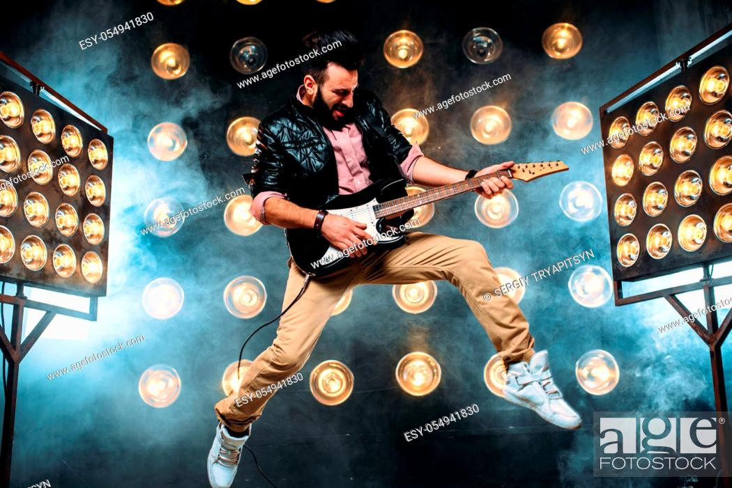 Imagen: Male pop star with electro guitar on the stage with the decorations of lights. Music entertainment.