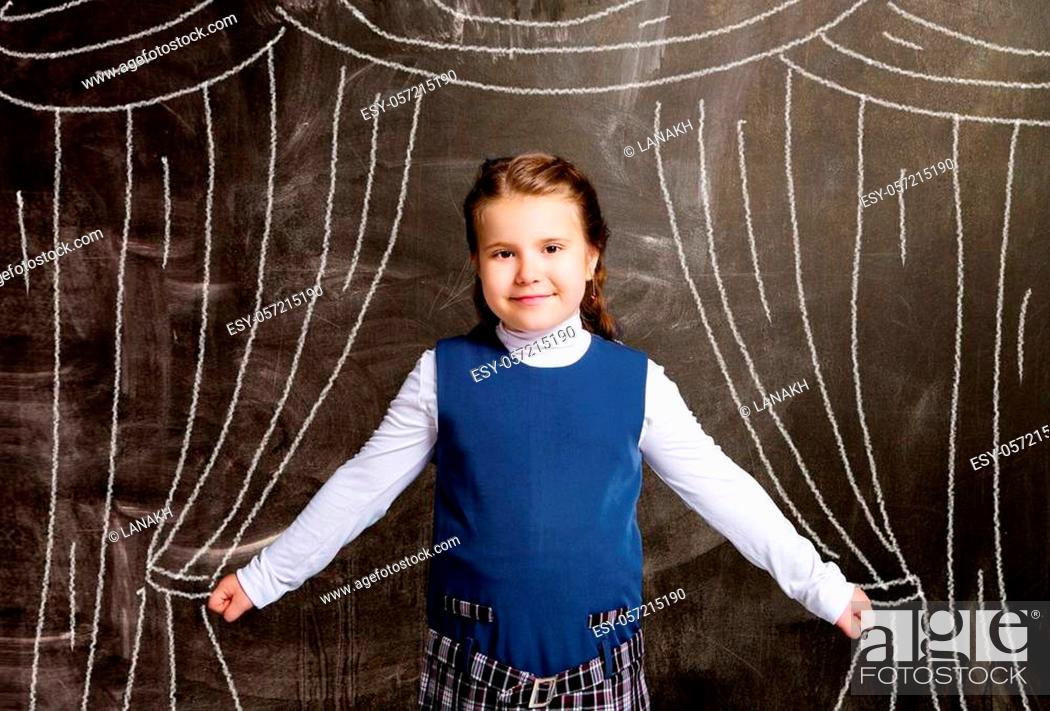Stock Photo: cute little schoolgirl against chalkboard, with drawn curtains.