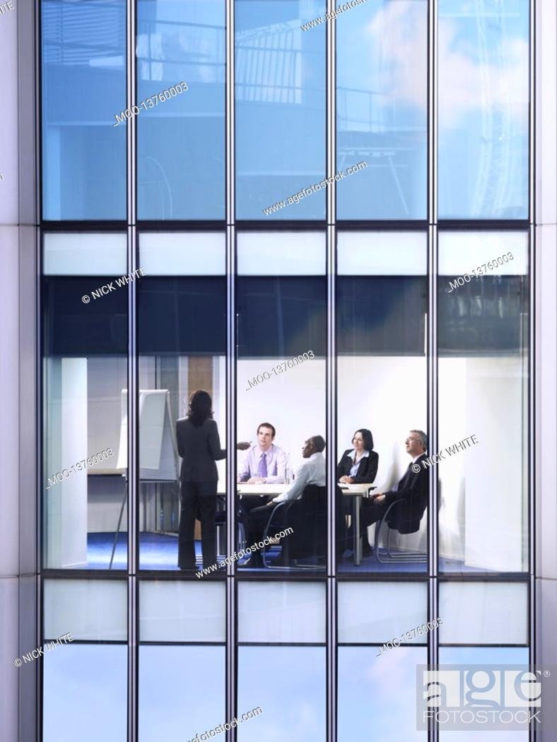 Stock Photo: Group of business people at meeting in office view from building exterior.