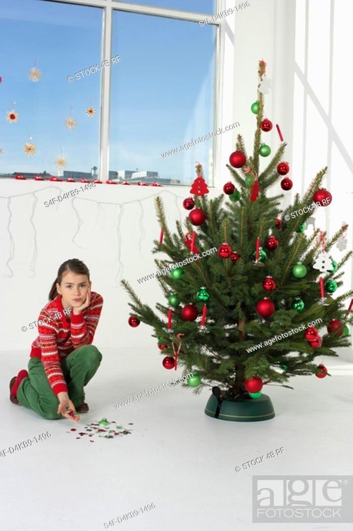 Stock Photo: Girl picking up Christmas tree ball shards.