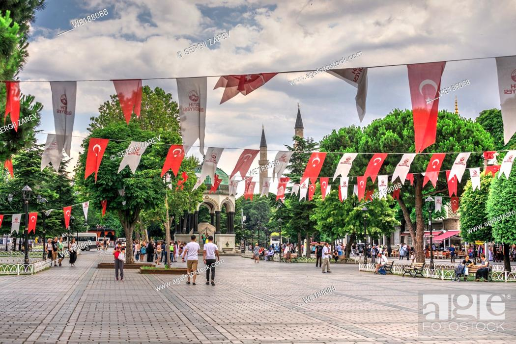 """Stock Photo: Istambul, Turkey â. """" 07. 12. 2019. Many tourists walk around Sultan Ahmet Park on the site of a former Hippodrome in Istanbul, Turkey, on a cloudy summer day."""