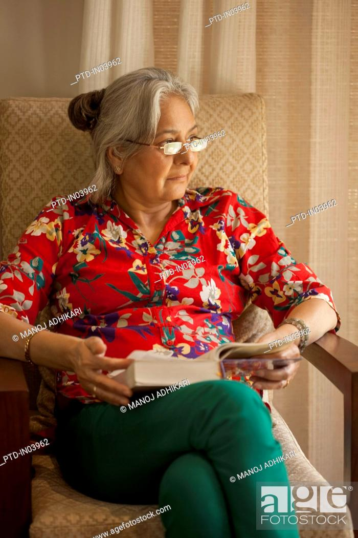 Stock Photo: India, Senior woman sitting in armchair reading book.