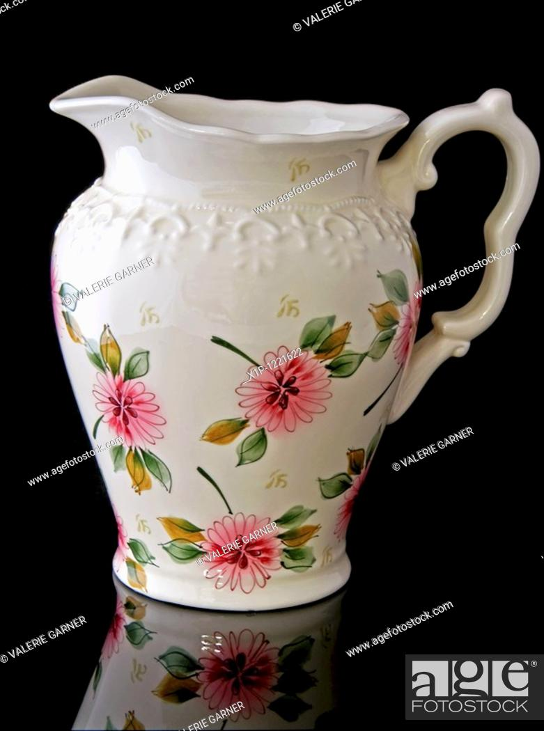 Stock Photo: This stock image is a cream colored, floral water pitcher for home decor accent use, isolated on a black background with a beautiful reflected image in the.