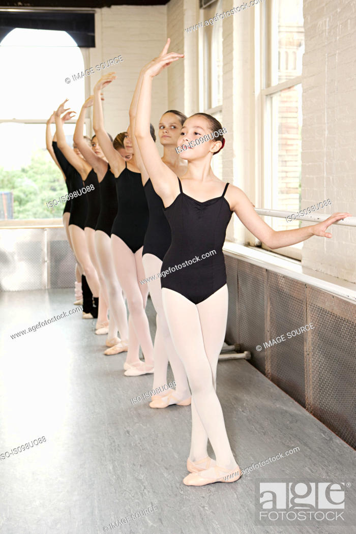 Stock Photo: Ballerinas in pose at barre.