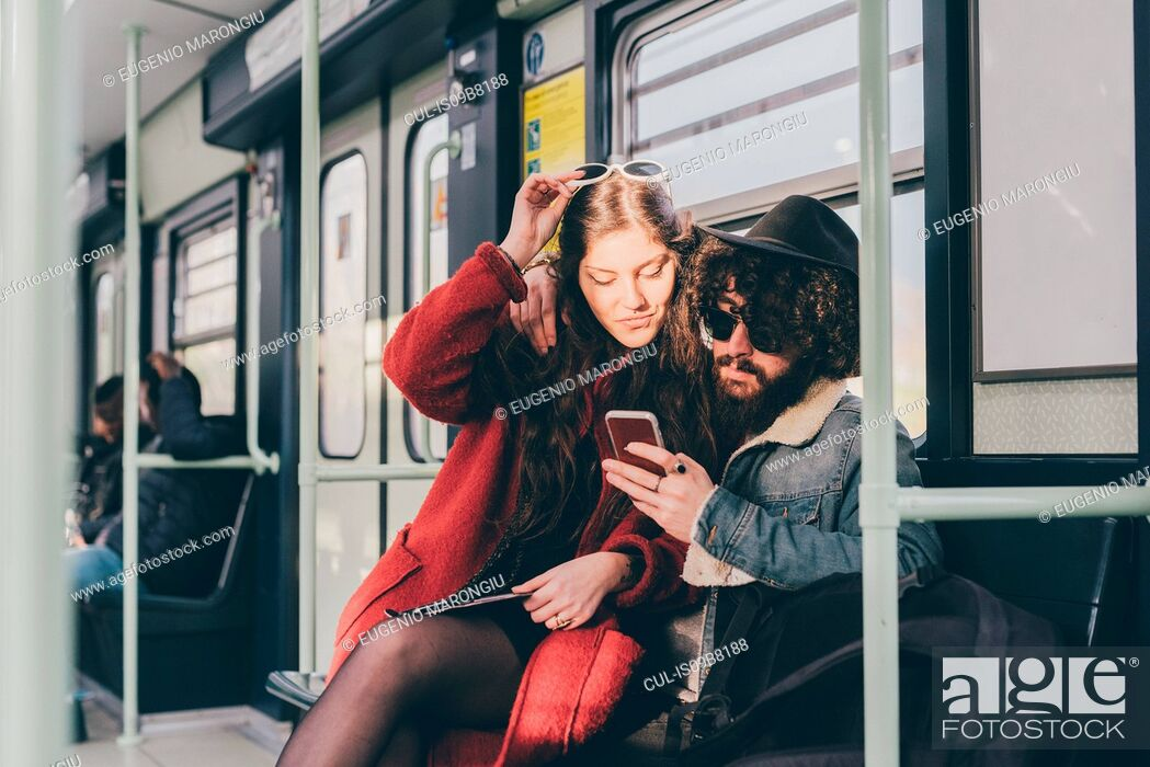 Stock Photo: Young couple sitting on subway train, looking at smartphone.
