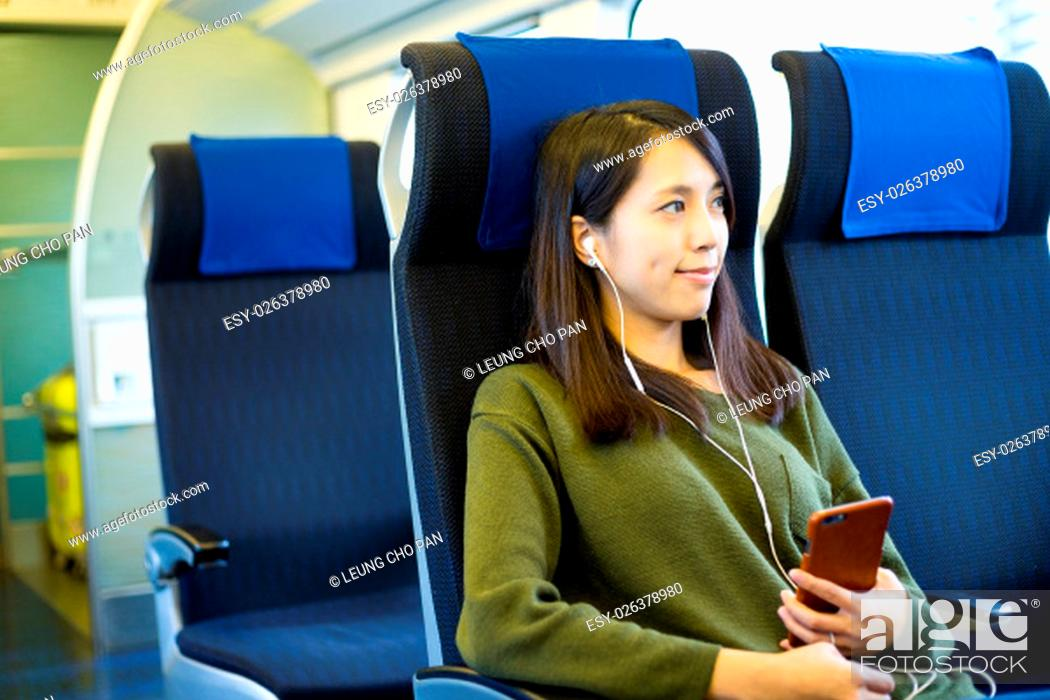 Stock Photo: Woman listen to music on mobile phone inside train compartment.