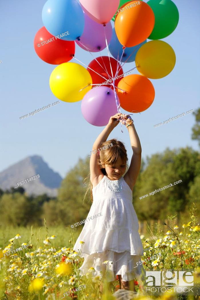 Stock Photo: Girl in meadow with balloons.